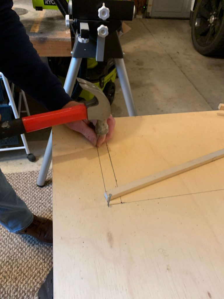 hammering a nail at the corner to create the pivot points for the DIY archway