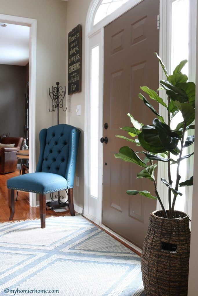 Front entryway with blue chair and plant in a modern vintage home tour