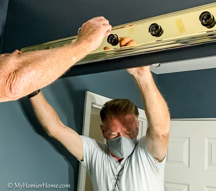 man removing light fixture pieces to spray paint