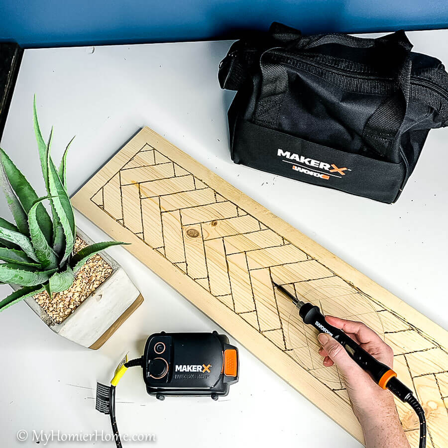 Use the MakerX wood & metal crafter tool to burn the wood herringbone pattern