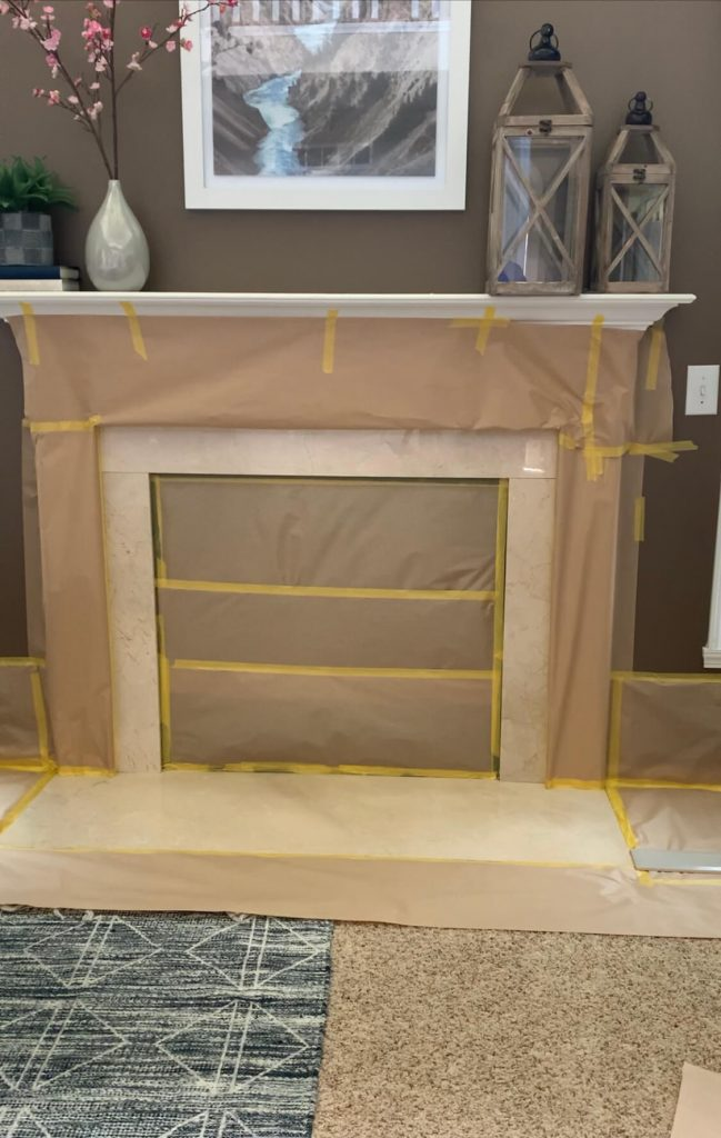 prepping with brown paper to spray paint fireplace surround