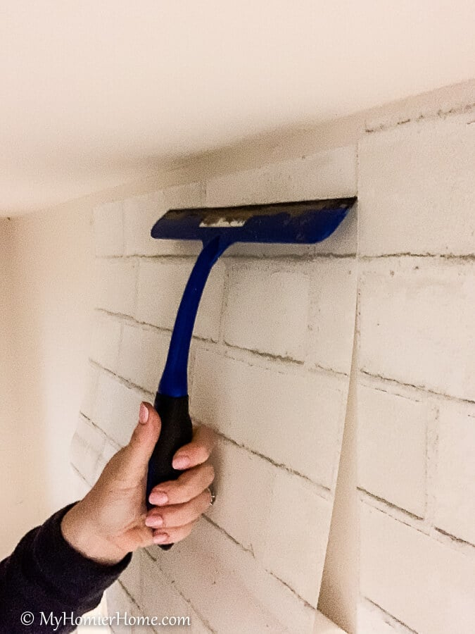 Squeegee from the center out to smooth the peel and stick wallpaper.