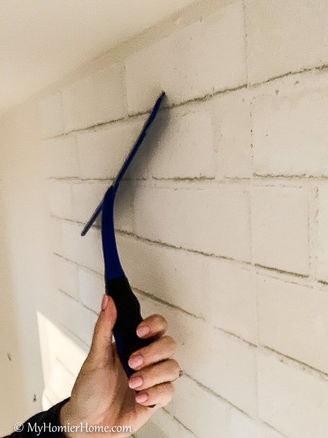 Squeegee the peel and stick wallpaper from the center out, smoothing it and pulling the backing off as you go down.