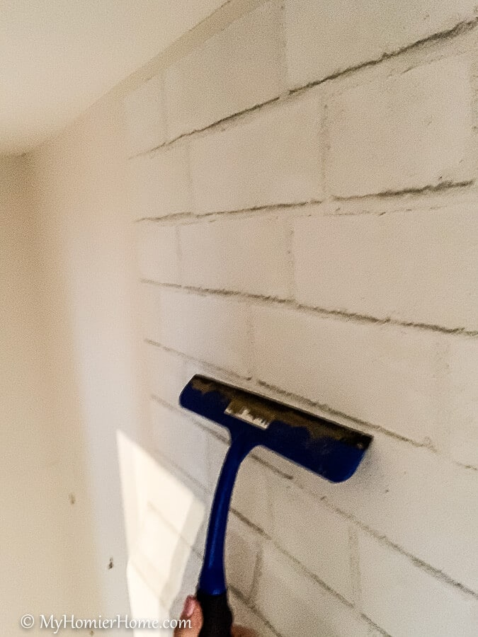 Continue the process of removing the backing and smoothing from the center out until you reach the bottom of the wall with your peel and stick wallpaper.