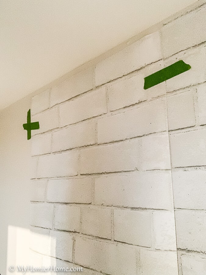 Tape the peel and stick wallpaper with painter's tape where you want to hang it.