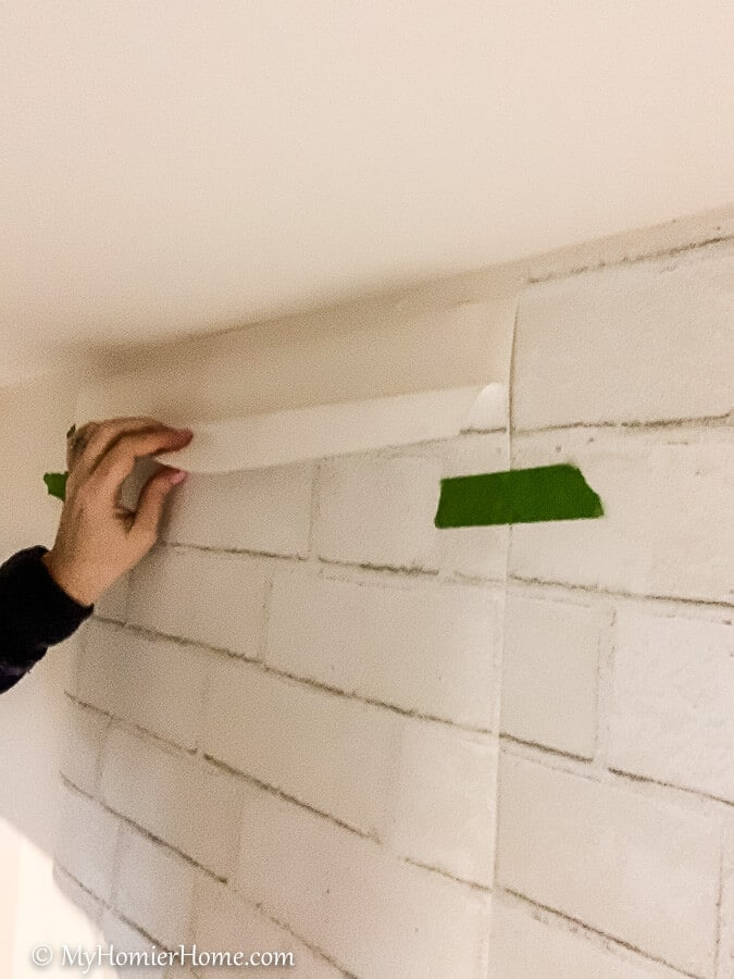 Take the backing off of the peel and stick wallpaper just at the top to start.